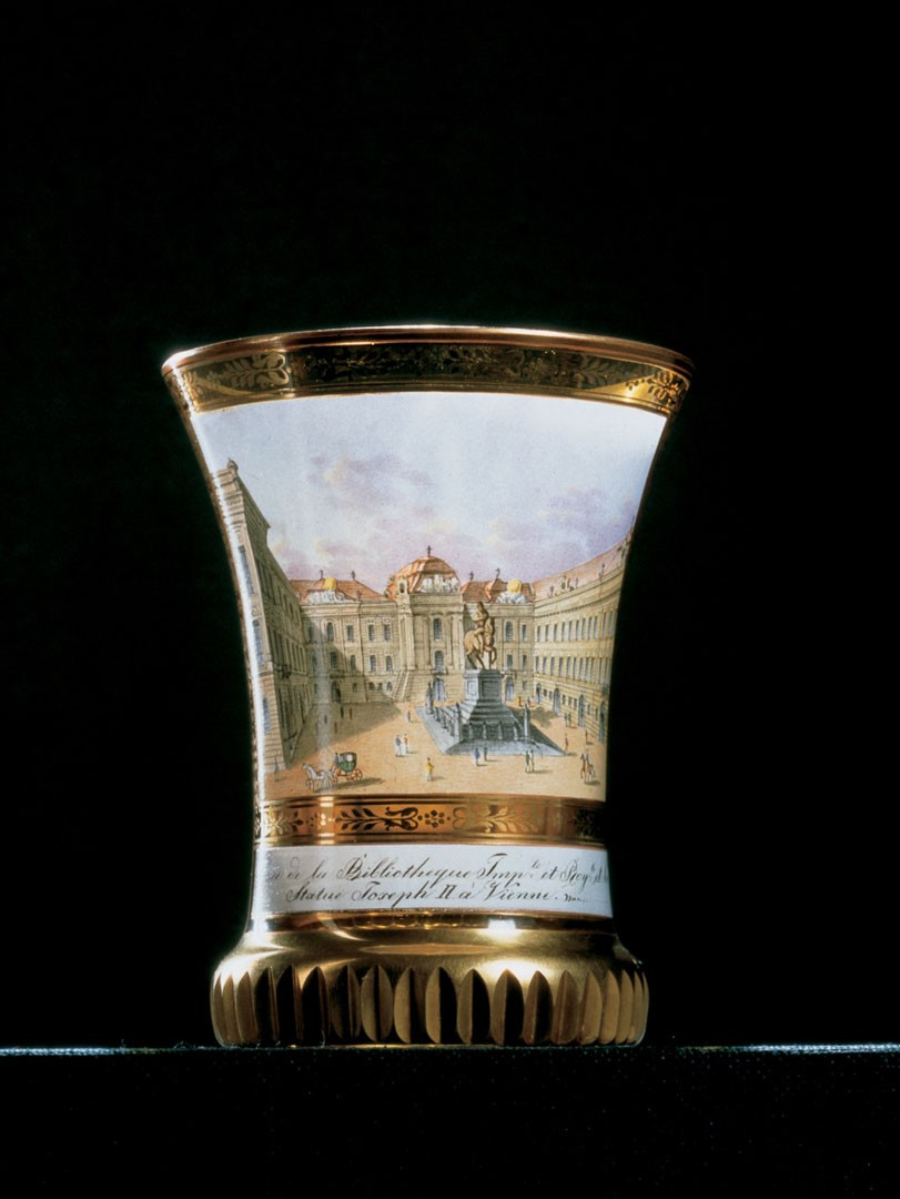 "<BODY><div>CUP</div><div>Vienna, ca. 1830</div><div>Design and Manufacture: workshop of Anton Kothgasser</div><div>Curved cup with fluted base, with enamel decoration and gilding; colored veduta painting in a rectangular, bordered field with inscription: ""Place de la Bibliothèque Imp.le et Roy.le et la Statue Joseph II à Vienne""</div><div>Gl 2365 / 1917</div></BODY>"